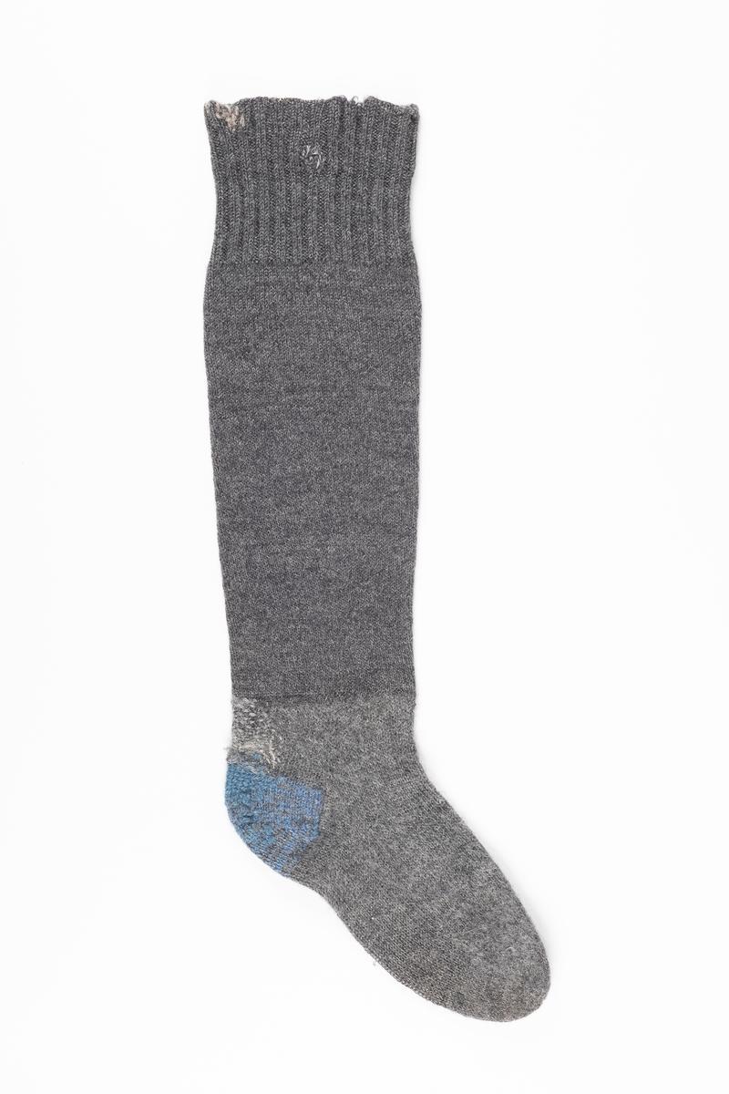 Ett par knestrømper strikket med grått ullgarn. Hælen er strikket med blått garn. På innsiden ved åpningen er det påsydd en lapp med fangenummer.