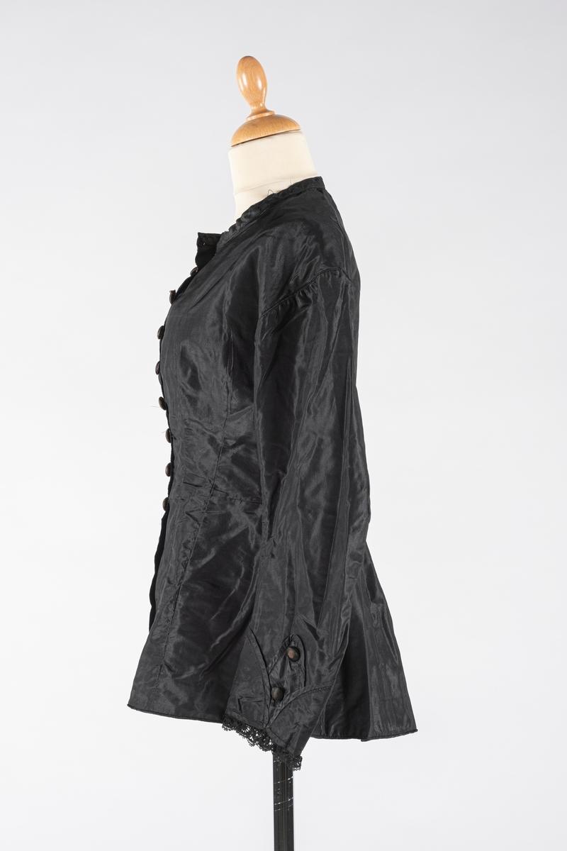 Sort kjoleliv, figursydd med lange ermer og lav krage. Hovedtøy av taft, innvendig foret med linlerret og bomullstøy i ermene. Det er ingen spiler. Dekor av sorte kniplinger påsydd rundt ermene og to tøy-overtrukne knapper. Tøy-overtrukne knapper og maskinsydde knapphull på fremsiden. Hempe av mørkegrønt stoff i rygg.