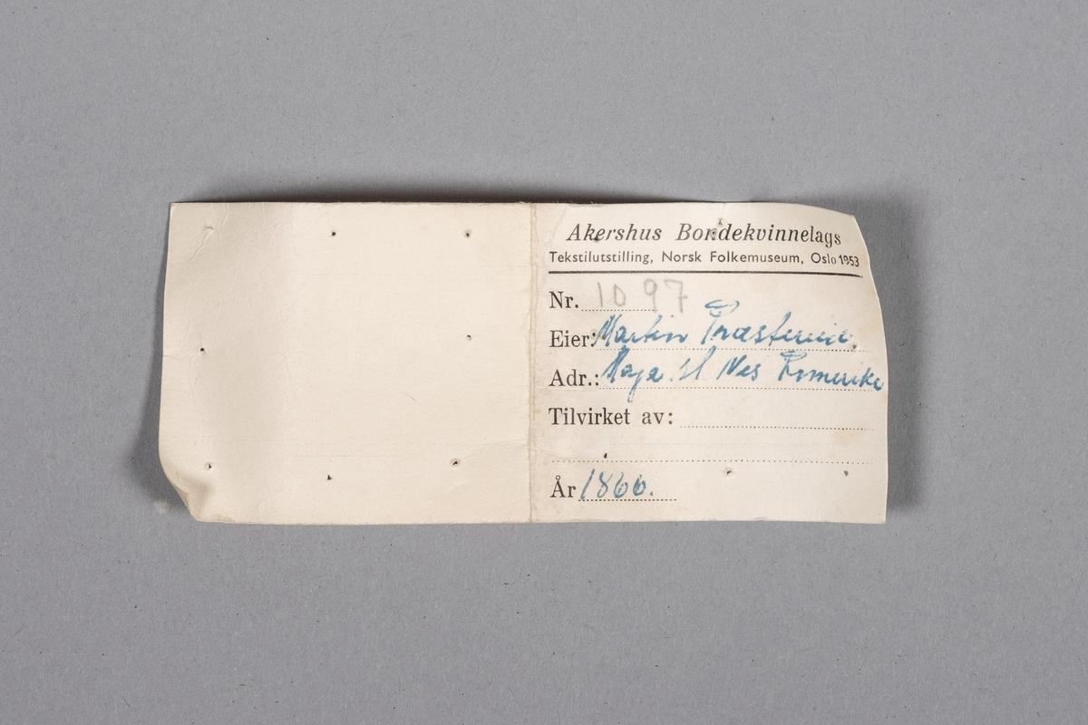 Etikett som ble brukt til tekstilutstillingen på Norsk Folkemuseum i 1953. Rektangulær, brettet i to, med skrift på fremsiden. Opplysninger om hvem som eier dåpskjolen, hvor eier bor, hvem som har produsert den, og når den er produsert.