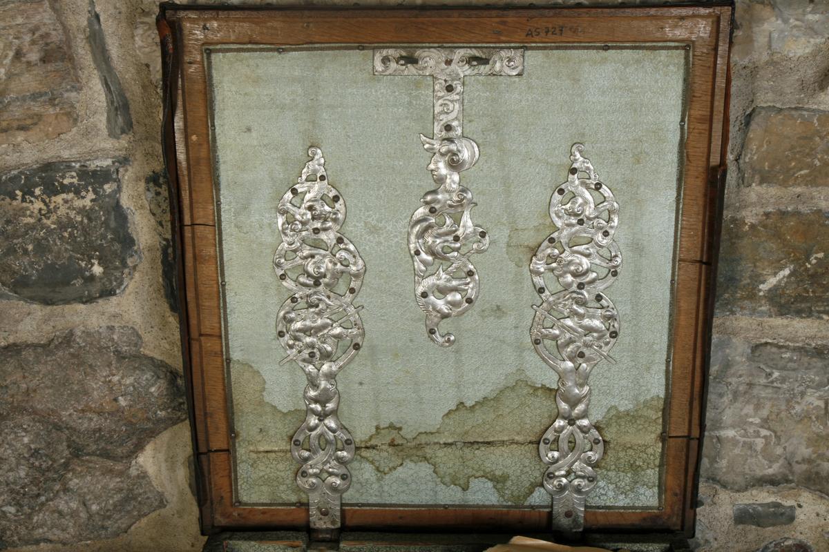 Eik, trukket med lær, fortinnete jernbeslag, beslagene rikt utformet med bl.a. ranker og norges løve, smijernshåndtak på sidene. Innvendig trukket med lysegrønn silkesateng.