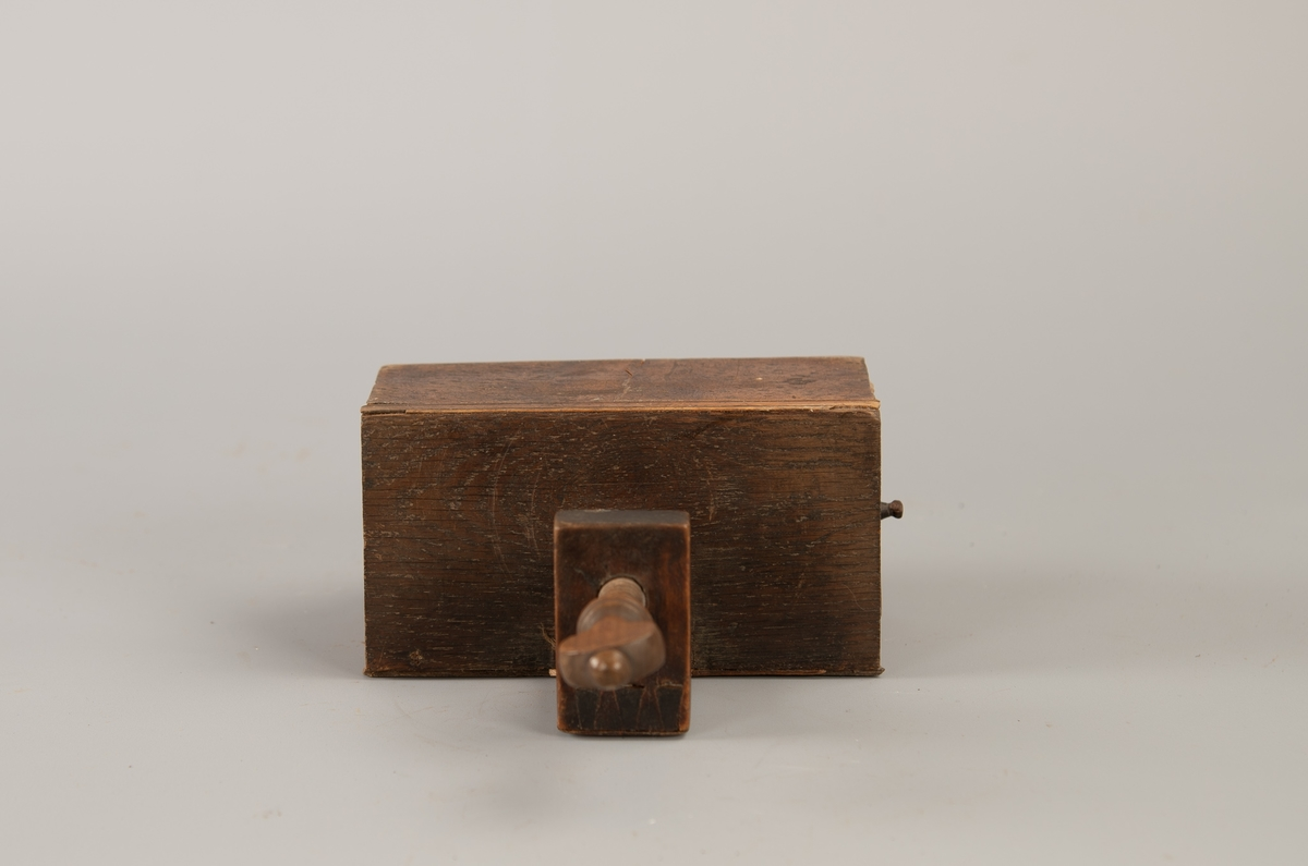 Rektangulær kasse med en skuff i den ene kortside,  i den andre mangler skuffen. Skrufeste på den ene lang side.  Eik,  delvis  finert med valnøtt og en stripe gult tre.   Skrue av eik, i vinkelbeslag av bøk.  Pute fyllt med hard sand og stoppet med lerret over, rester på sidene av mørkebrun fløyel.
