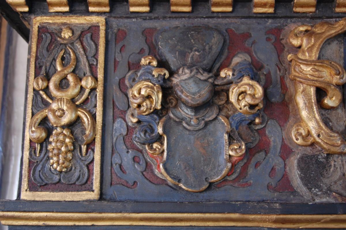 Kaminen dateres stilmessig til ca 1630-40 og har Christopher Urnes og hans hustru Sophie Lindenovs våpenskjold på gesimsen. Utskjæringer som forestiller ulike figurer både på sidene av kaminen og på gesimsen.