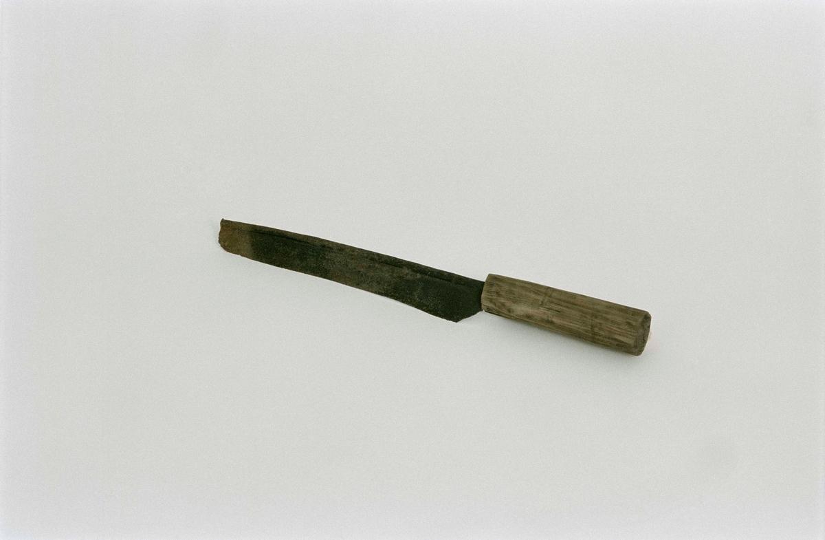 Kniv av järn, skaft av trä. Jämnbrett blad, inböjd kant upptill. För skörd av potatisblast, enligt huvudliggaren.