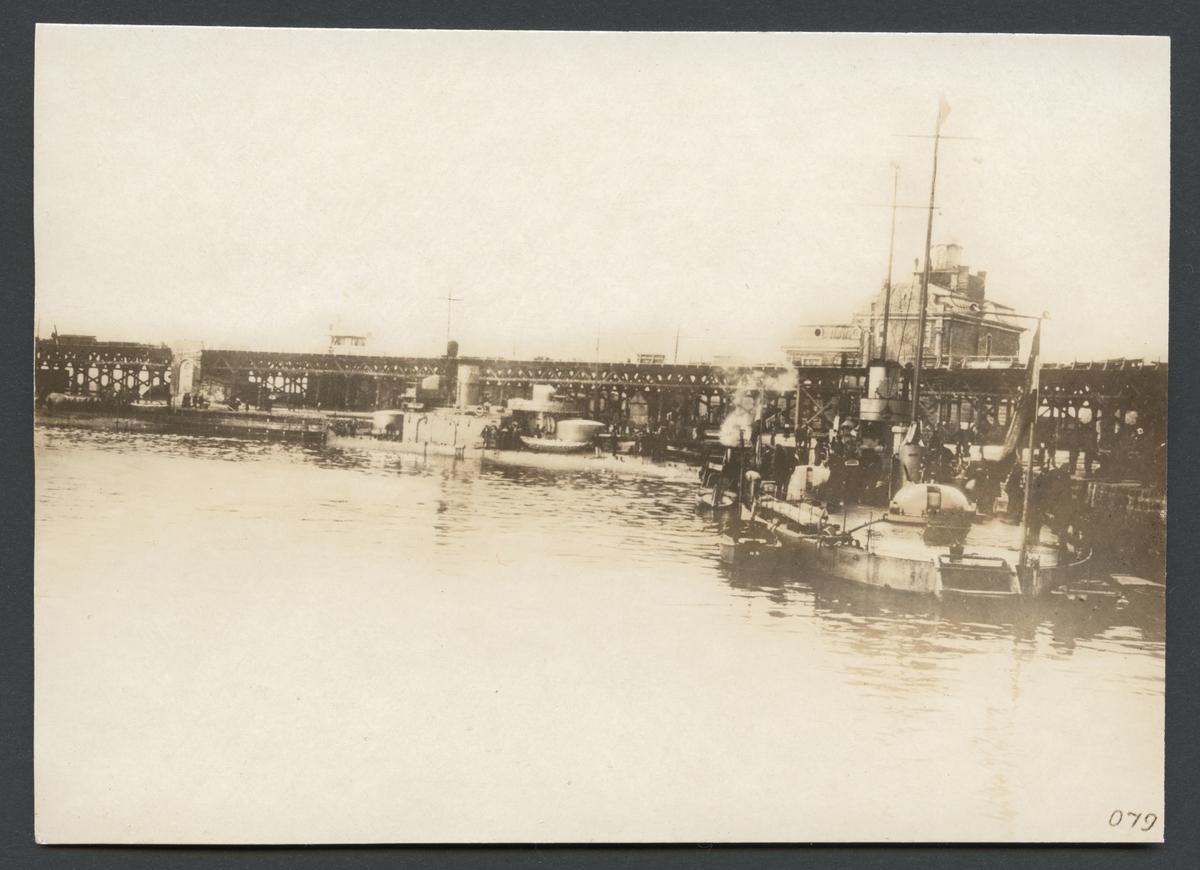 """Bilden visar hamnbassäng i Odessa med ett flertal örlogsskepp som ligger förtöjt vid kajen. I bakgrunden syns en stor träbro.  Originaltext: """"Krigsskepp, tillhörande K. K. Donau-flottiljen i Odessas hamn."""""""