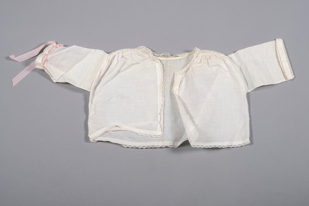 Jakke til dåpskjole i hvitt mønstret bomullstekstil. Åpen i front, ingen lukkemekanisme. Blonder i halskant, langs åpning, og langs nedre kant. Kniplinger i skuldre, og mellom mansjett og erme. Det er festet et rosa bånd i knipling på venstre arm, båndet er ikke originalt.