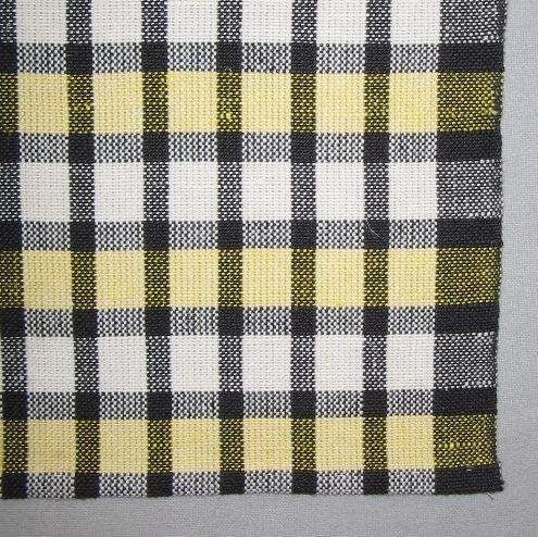 Rutig handduk, tre stycken, vävd i tuskaft med tvåtrådigt svart och blekt bomullsgarn i varpen och halvblekt, svart och färgat lintowgarn som inslag. Varpen är randig i smala svarta och lite bredare blekta ränder. Ytterkanten är svart. Inslaget är randigt på samma vis, med varannan smalare svart, men varannan bredare rand är halvblekt och varannan är färgad.  Handduken med inv.nr 0002:1 har gult inslag, inv.nr 0002:2 har rött och inv.nr. 0002:3 har blått. Det är en smal tråcklad fåll i vardera kortsidan samt ett smalt vitt bomullsband fastsytt mitt på kortsidan som hank.  Handduken med modellnamn Galler är formgiven av Ann-Mari Nilsson och tillverkad av Länshemslöjden Skaraborg. Den finns med  på sidan 10-11 i vävboken Inredningsvävar av Ann-Mari Nilsson i samarbete med Länshemslöjden Skaraborg från 1987, ICA Bokförlag. Se även inv.nr. 1,3-40.