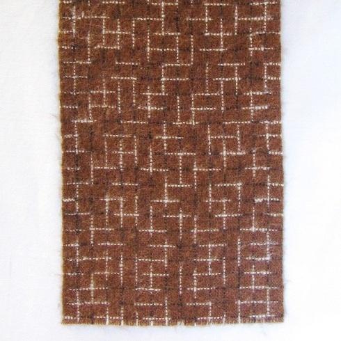 Halsduk vävd i tuskaft av ullgarn. Varpen och inslaget är enfärgat brun med rutor i flamfärgat garn i svart och vitt. Halsduken är endast avklippt och är lätt beredd.  Halsduken är formgiven av Ann-Mari Nilsson. Se även inv.nr.0111-0113 Halsduk samt inv.nr.0115 Vävprov i andra färgställningar.