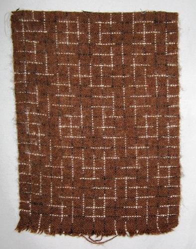 Vävprov, halsduksprov, vävd i tuskaft av ullgarn. Varpen och inslaget är enfärgat brun med rutor i flamfärgat garn i svart och vitt.  Vävprovet till halsduk är formgivet av Ann-Mari Nilsson. Se även inv.nr.0111-0113 Halsduk i andra färgställningar.