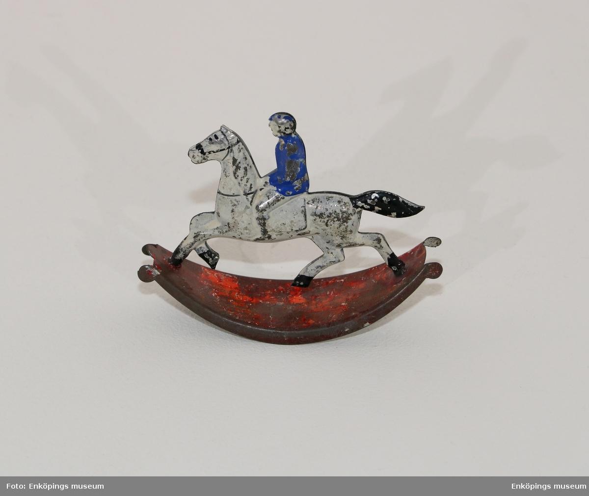 Ryttare med blå hjälm och rock på vit häst. Rödmålad under det så att leksaken kan gunga.