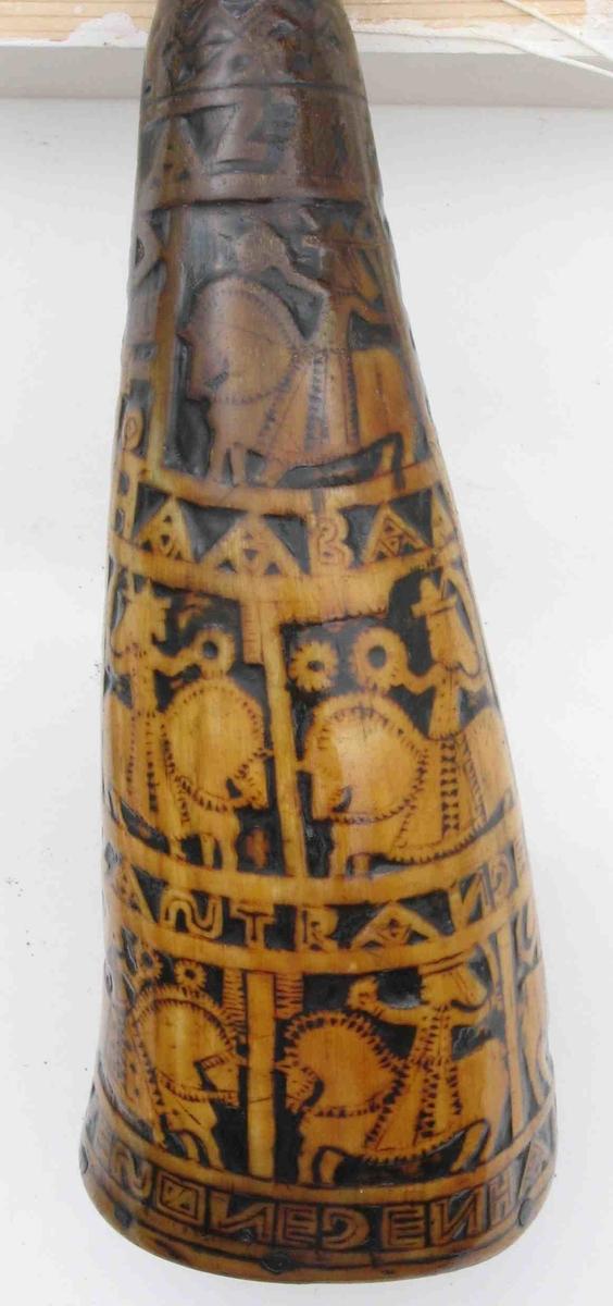 Krutthorn 1777  Andres Olvesøn egen han    Rundt horn, aller øverst mørknet, avskavet og forsynt  m. fals og liten messingholk, flat treplate i bunnen, klosset skåret JENH 1777. Vanlige små firk. skårne figurfelter m. innskr.: ADAMENMAN EVAENKVINDE OTEV-AL BVRM OLGER HAABA FIRAKONOLASTR ANGESØN   ANDRESOLVESØNEGENHAN: Oteval, muligens Otvel, en av motstanderne til Karl den Stores menn; Burman; Holger Danske; HAABA, ant. Hagbart som er Olaf Strangesøns Motstander. Tilst. juni 1961: Lakkert over m. tykk klar lakk, propp mangler.