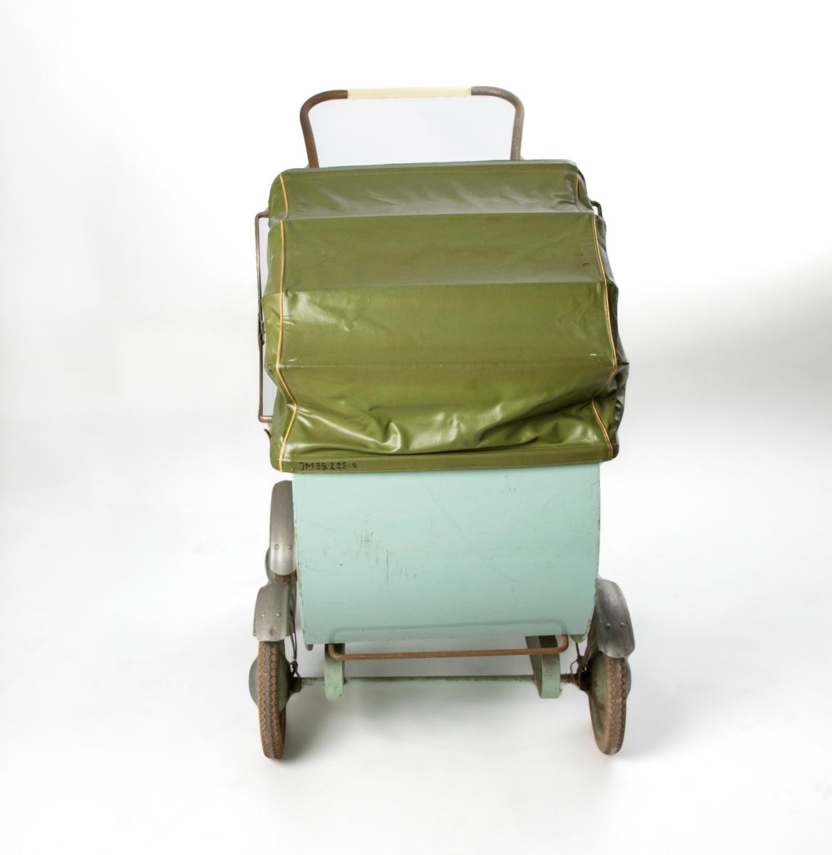 """Ljusgrön barnvagn av trä med rundade nederkanter, delvis rostigt handtag, vit plast i framkanten. Firmamärke: """"F Ö (däremellan en figur), svensk tillverkning"""". Grönmålade gummihjul med stänkskärmar av plåt. Till vagnen hör även sufflett JM 35.225:2, löstagbart av grön nylon, och vindskydd JM 35.225:3 av grön galon med fönsterruta av genomskinlig plast. Fjädringen hålls uppe med hjälp av läderremmar som sitter mellan fram och bakhjulen på vardera sida.  Vikt: 18,2 kg."""