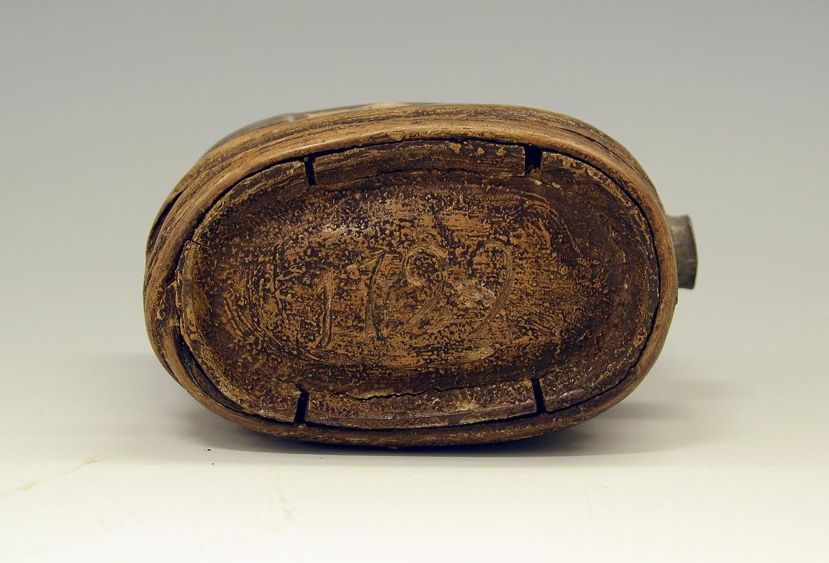 Brennevinsflaske. Fra protokollen: Lommeflaske lagget av træ som en bitte liten holk; konvekse bundstykker, spundstut paa siden. Paa den ene bunden skaaret 1729. Paa anden bund ulæselige bokstaver. (R. Berge)