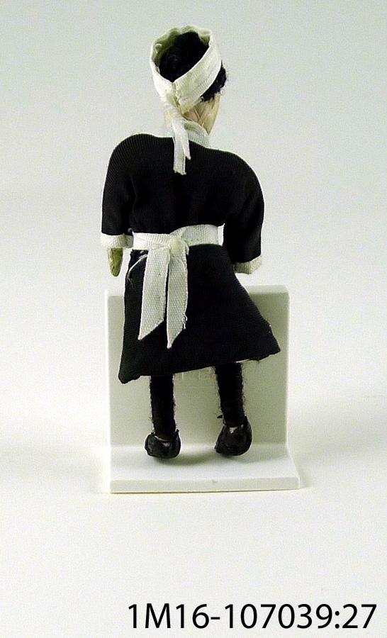 Docka, med svart klänning med vit krage med en röd glaspärla på, vita manschetter, vitt förkläde, vit huvudbonad, vit underkjol med hålsöm, vita underbyxor med spetskant. Benen är virade med svart ulltråd, svarta skor. Målat ansikte på tyg, svart hår. Tillverkad av Anna Rönne.