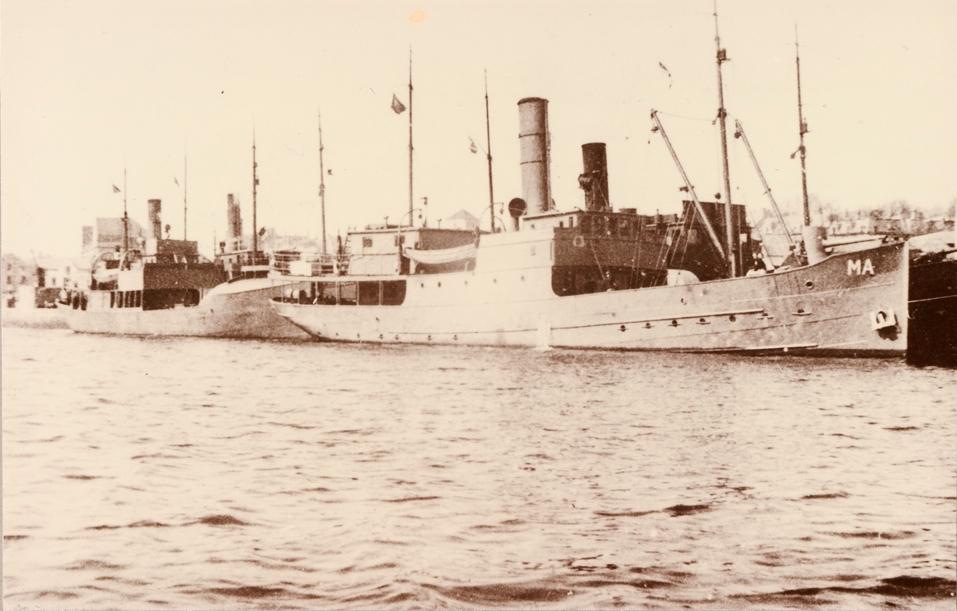 Motivet viser DS OSTER (bygget 1908), kystlandskap i bakgrunnen.