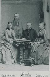 Familiegruppe med to kvinner og en mann som sitter ved et bo