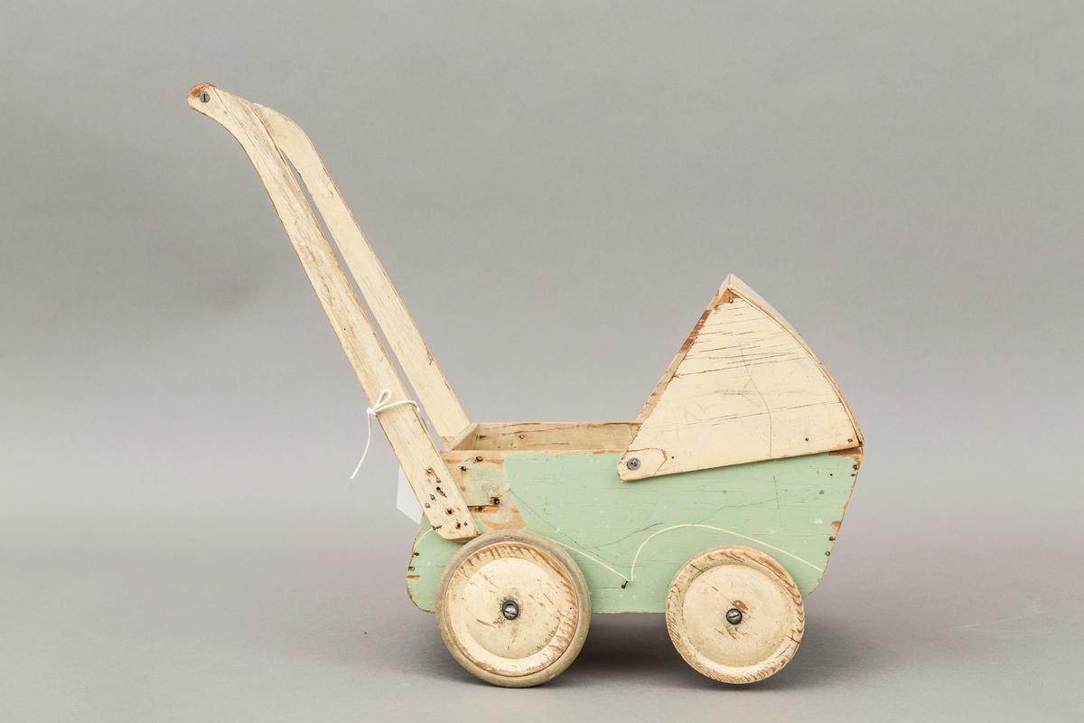 Dukkevognen er laget av finer. Hjulene på vognen er hele og er skrudd fast med jernskruer. Det er en firkantet form på selve vognen, og det er laget en justerbar kalesje som er festet til vognens øverste kant. Endel synlige slitasjer og skader.
