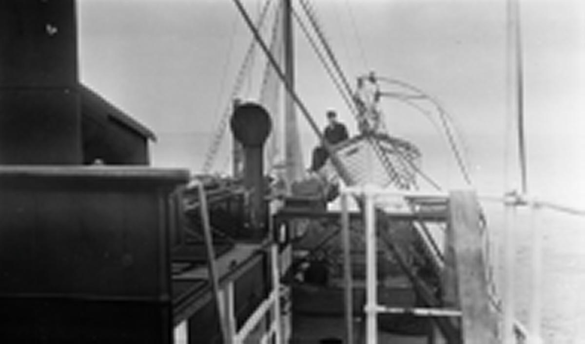 Ombord på D/S STORFOND sett mot akter. En mann sitter i livbåt som henger i daviter. Lastet med koks.
