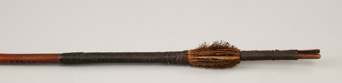 Bred spydspiss med markert rygg, nedhengende spiss i hver side. Pilpiss festet med sølvbånd, nederst med fjær, omviklet  med sorte fibber  Treet ujevnt i konturen, men helt glatt.