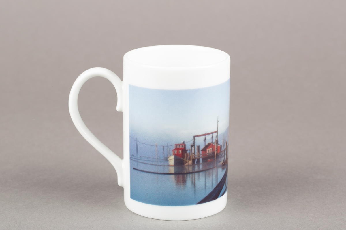 Krus med hank. Fetsund Lenser. Logo med to tømmerhaker, fugl og fisk. Fler farget motiv (foto): Båt med rødt styrhus, to røde buer på elva.