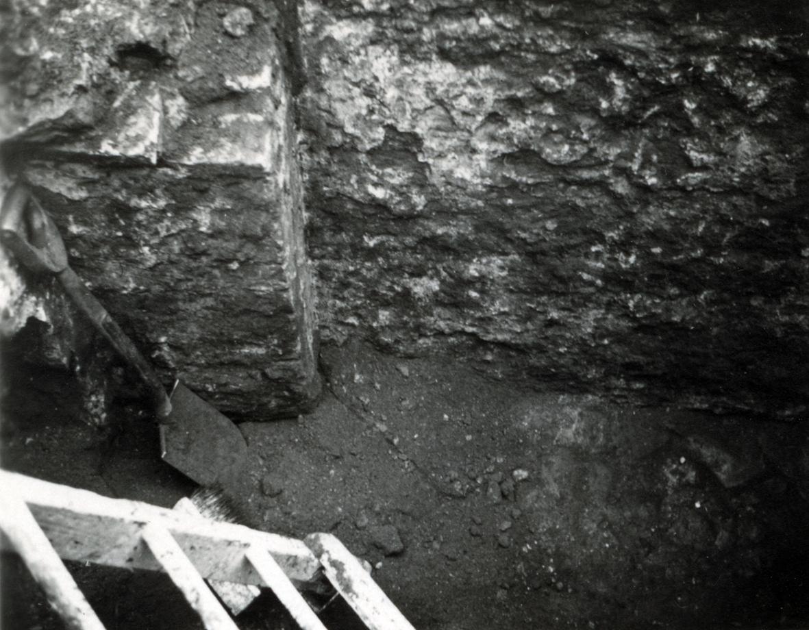 Murrest nordväst om trappan med golv av kullersten. Tegelpelare med rest av anfang för valv eller båge.