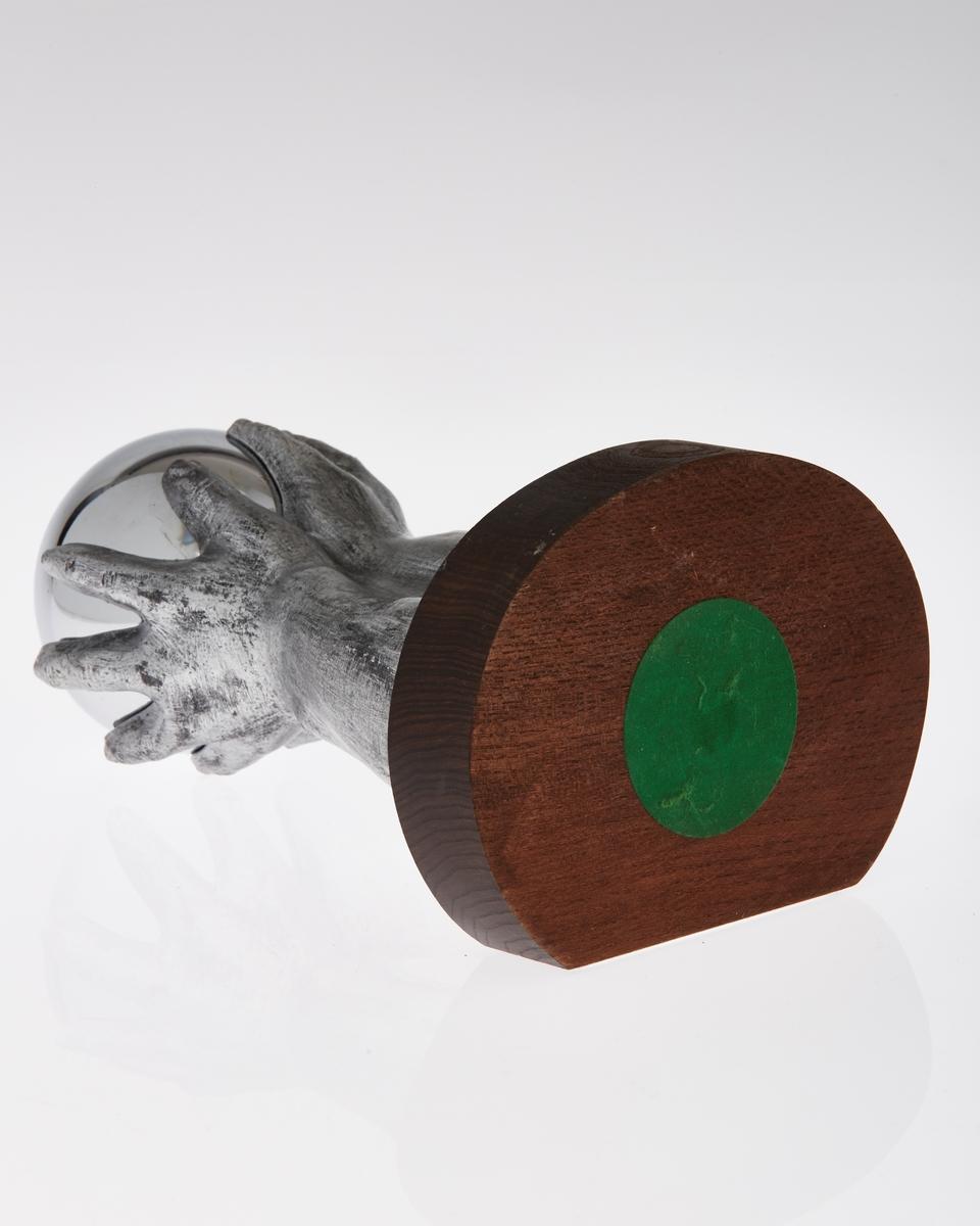 Pokal på stett. Stetten er av treverk, mens resten er av metall. Utformet med en åpen kule på toppen holdt av to hender. Emblem med to fotballspillende gutter.