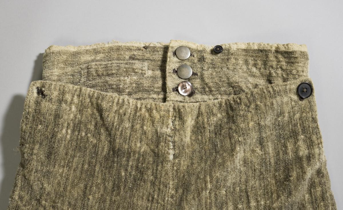 Beige knebukse av plysj, med knapper i linningen og ved knærne.