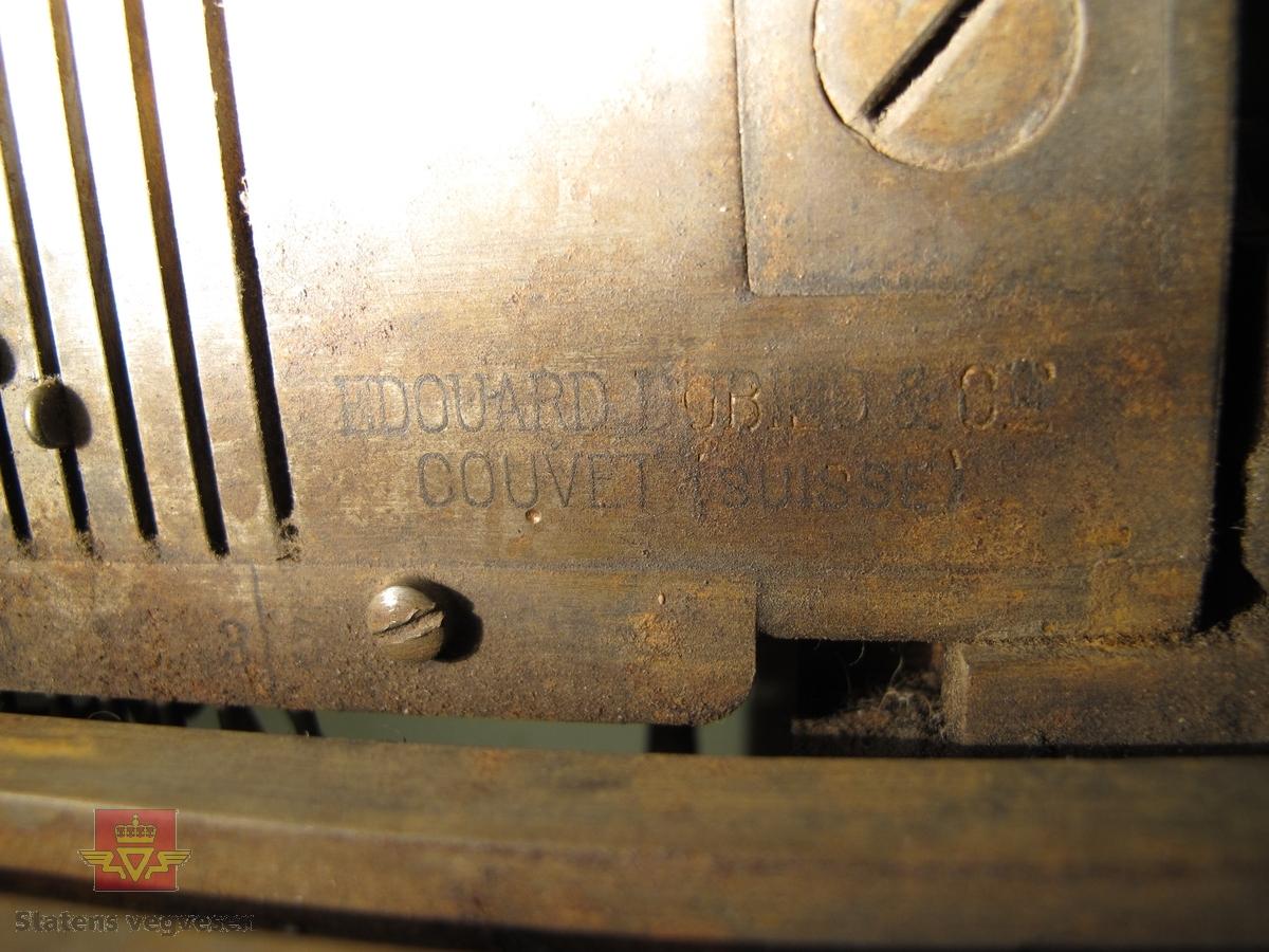 """Svært kompleks mekanisk innretning med mange deler, funksjoner og innstillinger. Avlang med to føtter for montering på bordplate e.l.  Noe støpejern, noe annet metall og trehåndtak på enkelte deler. En del skruer og justeringsmekanismer er merket med tall, symboler og bokstaver. Maskinens strikkemekanisme består av mange """"kroker"""" langs en skinne, der krokenes lengde kan stilles inn manuelt, muligens for maskebredde. Trolig er det slik at maskinen kan produsere en hel rad med masker når man drar i den store spaken."""