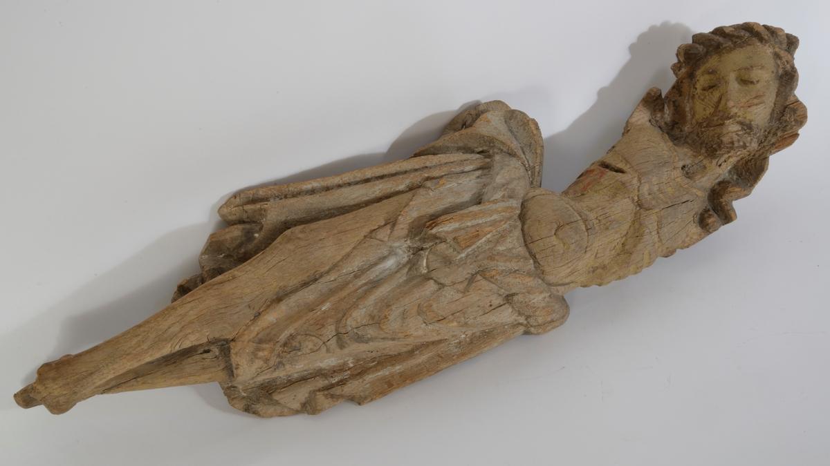 Kristus figur; fra krusifiks, kroppen svunget, hodet lagt over mot v., skjegget, lendeklede m. spor av hvit maling, rødm. fra lansestikket. Kryssede ben