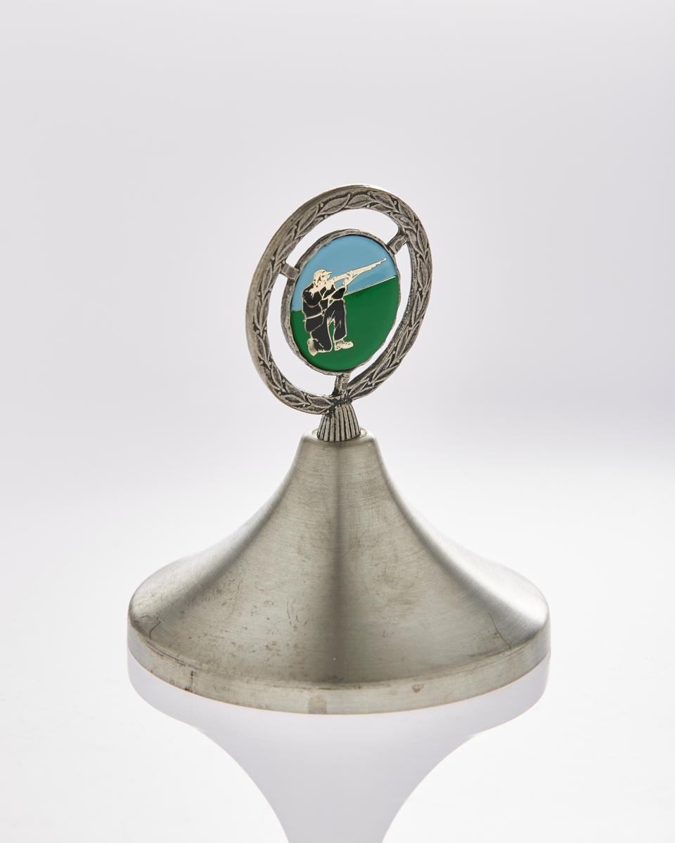 Emblem: Sirkulært, emaljert i sort, blått, grønt, sølv- Bilde av en skytter.