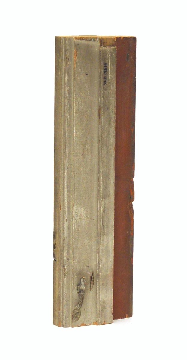 Kat. kort: Mittpost, trä. Från fönster vid Gamla Grand. Profilerad. Målad röd och grå. 2 st stjärthakar. L: 32,5 B: 9