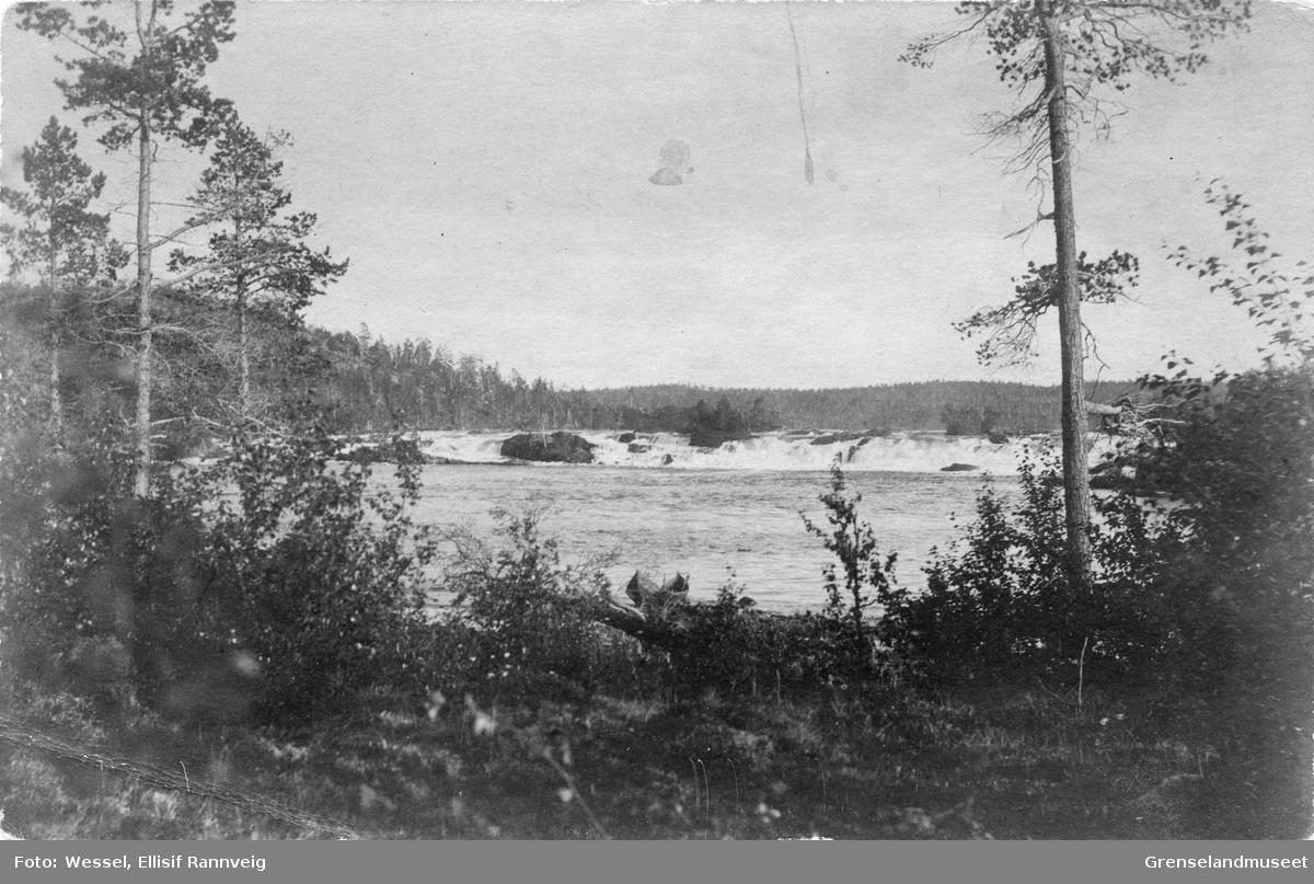 En elvebåt ligger på elvebredden i Pasvikelva, Skogfossen (Männikafossen) i bakgrunnen.