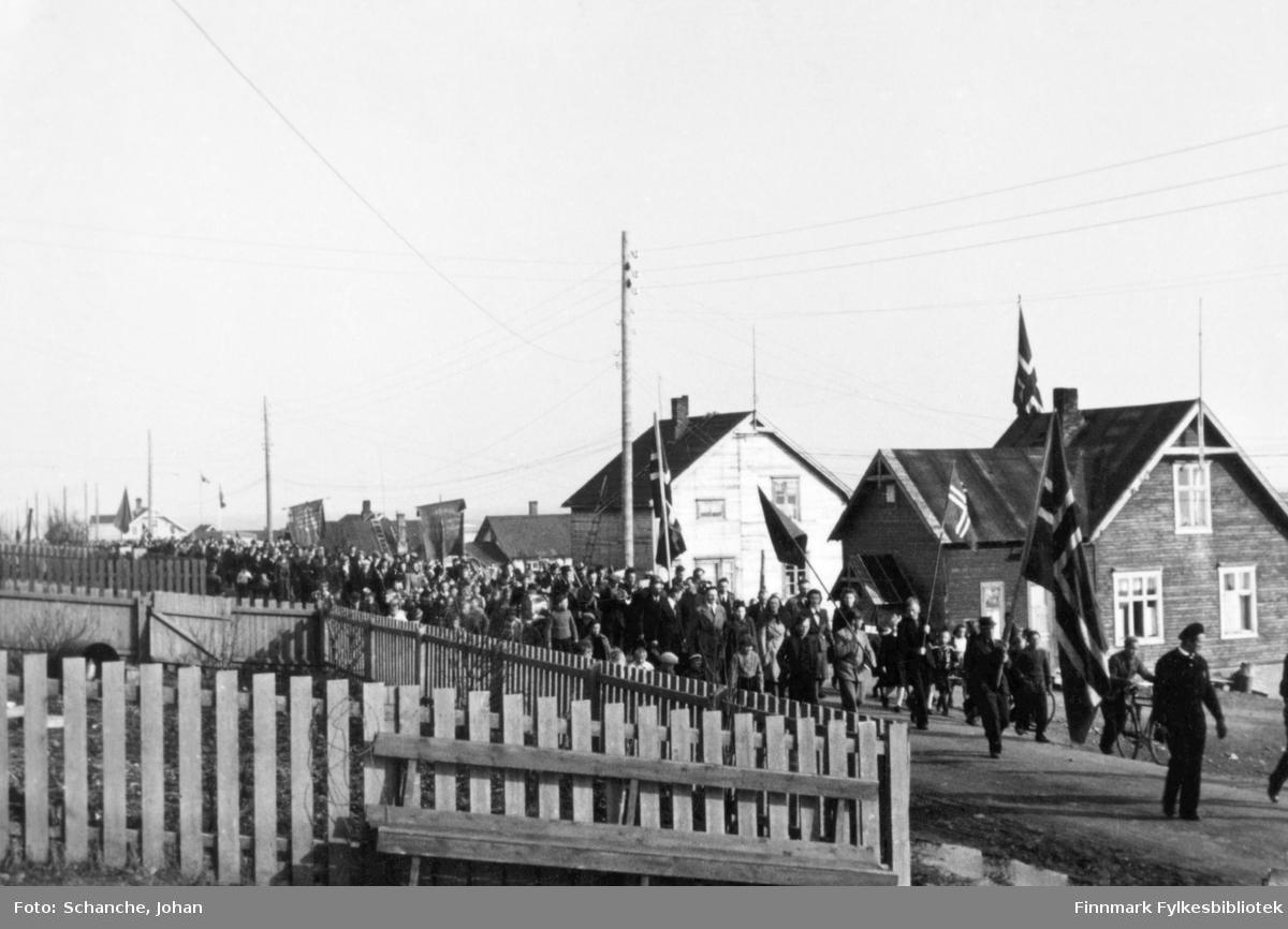 17.mai 1945 eller 1946 i Vadsø. Bildet viser et 17.mai tog som går langs Nyborgveien.   Huset nærmest tilhørte Isak Basma, senere overtatt av datteren Alfhild Basma. Så kommer huset til Eugenie Lakkala (født Berravara). Hennes sønner Erling og Hans Lakkala overtok huset i 1942.