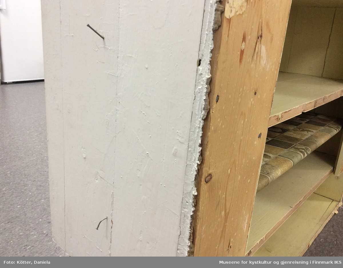 Dette vegghengte overskapet er en del av en kjøkkeninnredning som består av tre sammenhørende møbler. I tillegg til skapet er det en kjøkkenbenk med vask og en kjøkkenbenk med benkeplate.  Skapet har to blå malte dører av mdf-lignende materiale og et smalt, liggende fag nederst. Faget er dekket med en klaffe som forespeiler to skuffer. Skapets sidene er laget av trebord som er sammenføyd med not og fjær. Møbelkroppen, som er malt hvit utvendig, er utstivet med to loddrette bord på baksiden. Disse er festet med spikre i både sideveggene, men også i hyllene. Skapet er malt lysegult innvendig og har fire hylleplater. Hyllene består av to sammenføyde bord hver. En av hyllene har ikke full dybde og kan være tilføyd senere. Den er ikke føyd inn i en not i sideveggene, men ligger på smale lister som er påspikret på innsiden av sideveggene. Denne hylla er også overtrukket med en grønnmønstret voksduk. På begge sider av møbelkroppen er det slått inn spikre, mest sannsynlig til å henge opp kjøkkenredskaper.