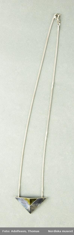 Halsband i silver med ett hängesmycke i form av en svagt konvex trehörning i silver med delvis guldplätering. Trehörningens spets pekar nedåt. Kedjan är en tunn pansarlänk. Hängsmycket är handgjort av Anna Christina Hultberg Graverad med designerns  namn AC Hultberg samt samt stämplad BEH 925 och  925 CCC. Kartong NM.0334489 a-c hör till halsbandet.  /Cecilia Wallquist 2019-02-21