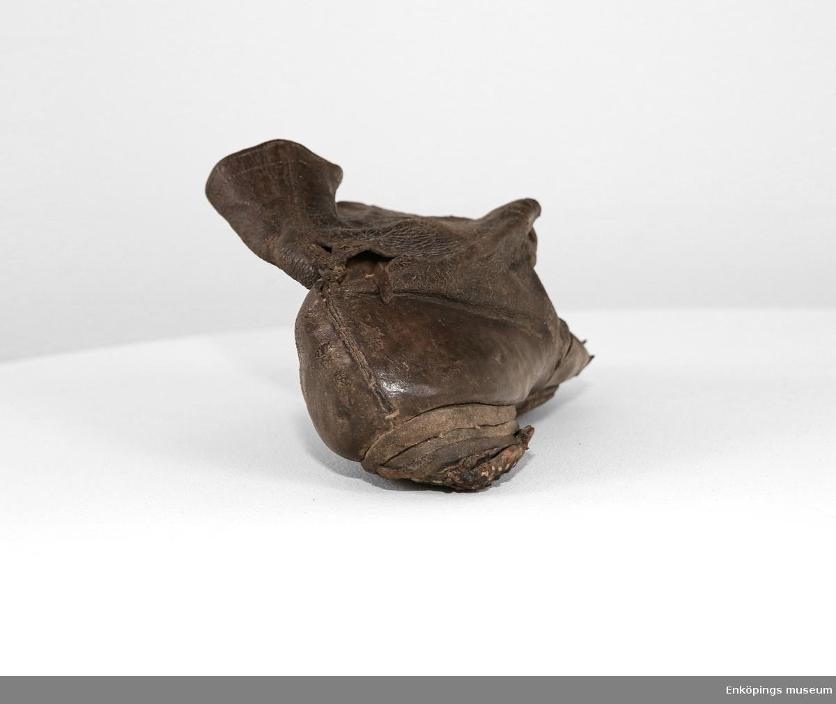 Känga av brunt läder med snörning framtill (saknar plös), tillverkad av två stycken, 9 par förstärkta snörhål. Har haft liten klack, sula och klackpliggade fast vid skaftet. Fodrad med beige kyprat bomullstyg och ett beige och lilarandigt tyg. Tillverkad efter 1840.