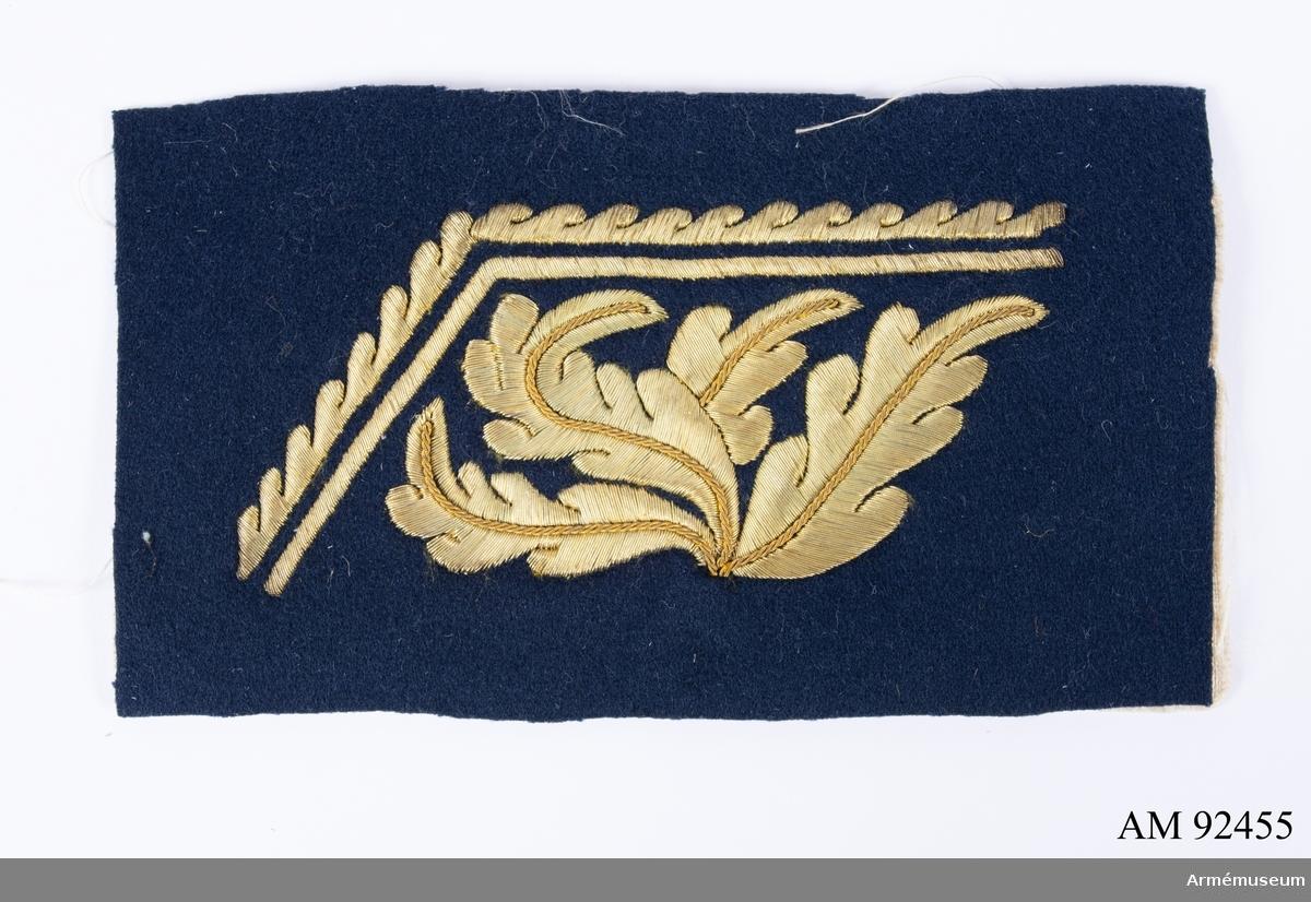 Mörkblått kläde med guldbroderi föreställande eklöv med en kant.
