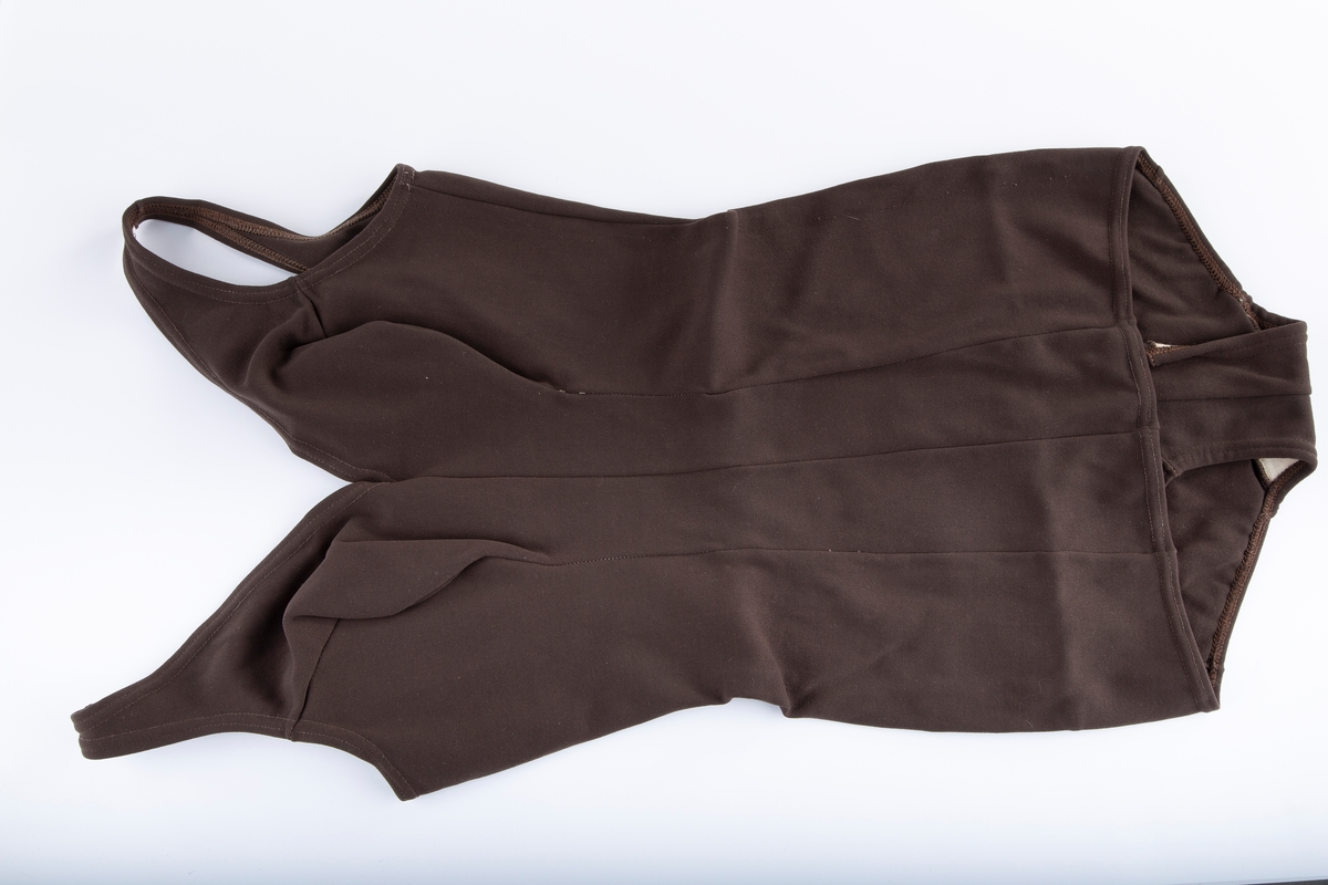 """Helskåret 6bredder. Stretch-stoff. To stropper, nylon innlegg ved bryst. """"Skjørt"""" over skrittet foran. Merke Helanca. str. 44"""