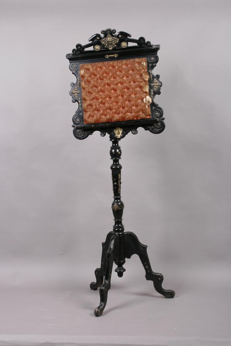 Notestativ i sortmalt tre. Notestol og fot kan settes sammen, foten deler seg i tre nederst. Rike profileringer på fot og stol, messingbeslag som er hamret i naturalistiske og stiliserte ornamenter. Stolen er på forsiden trukket med rustrødt, stoppet sikestoff. Denne kan reguleres på baksiden. Her kan men se merker etter to lister som sannsynligvis er det gamle festet mellom stol og fot.