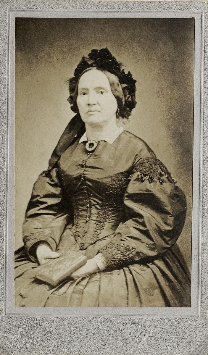 Foto av en kvinna i mörk sidenklänning med mörk hårklädsel. Vid kragen syns en stor brosch. Hon håller en bok i händerna. Knäbild, halvprofil. Ateljéfoto.