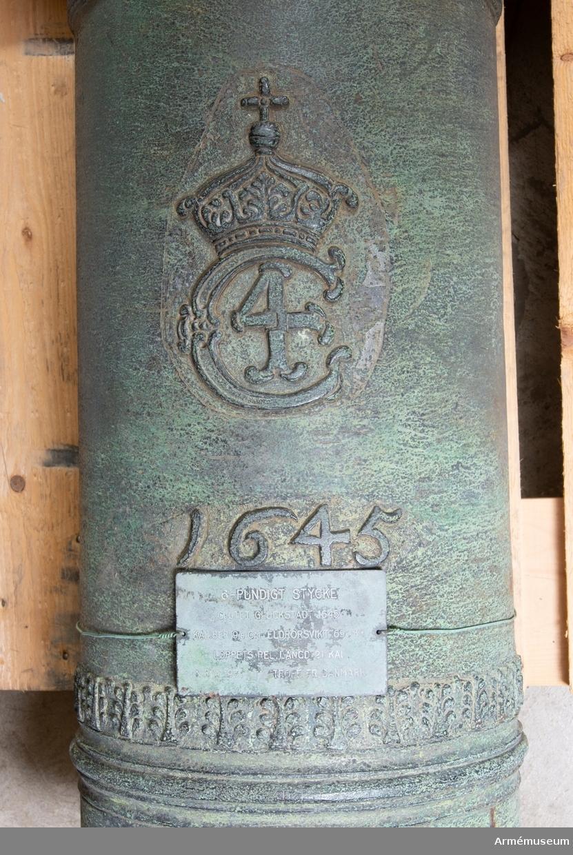 """Grupp A I.  Antagligen byte från intagandet av fästningen Glückstadt i Holstein den 5 januari 1814. Med Kristian IV:s namnchiffer och därunder gjutåret 1645; å kammarbandet inskriften: FRANCISCUS. ROEN. ME. FECIT. GLYCKSTADT. (Frans Roen gjorde mig i Glückstadt) Loppets relativa längd: 21 kal.  Kaliber: 9,8 cm. Deuvhalsen märkt """"4"""", vänster tapp märkt """"1""""."""