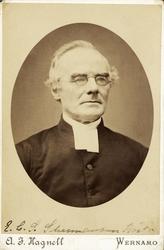 Foto av en äldre man med glasögon, klädd i prästrock med prä