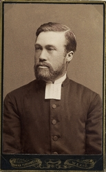 Foto av en man med helskägg, klädd i prästrock och prästkrag
