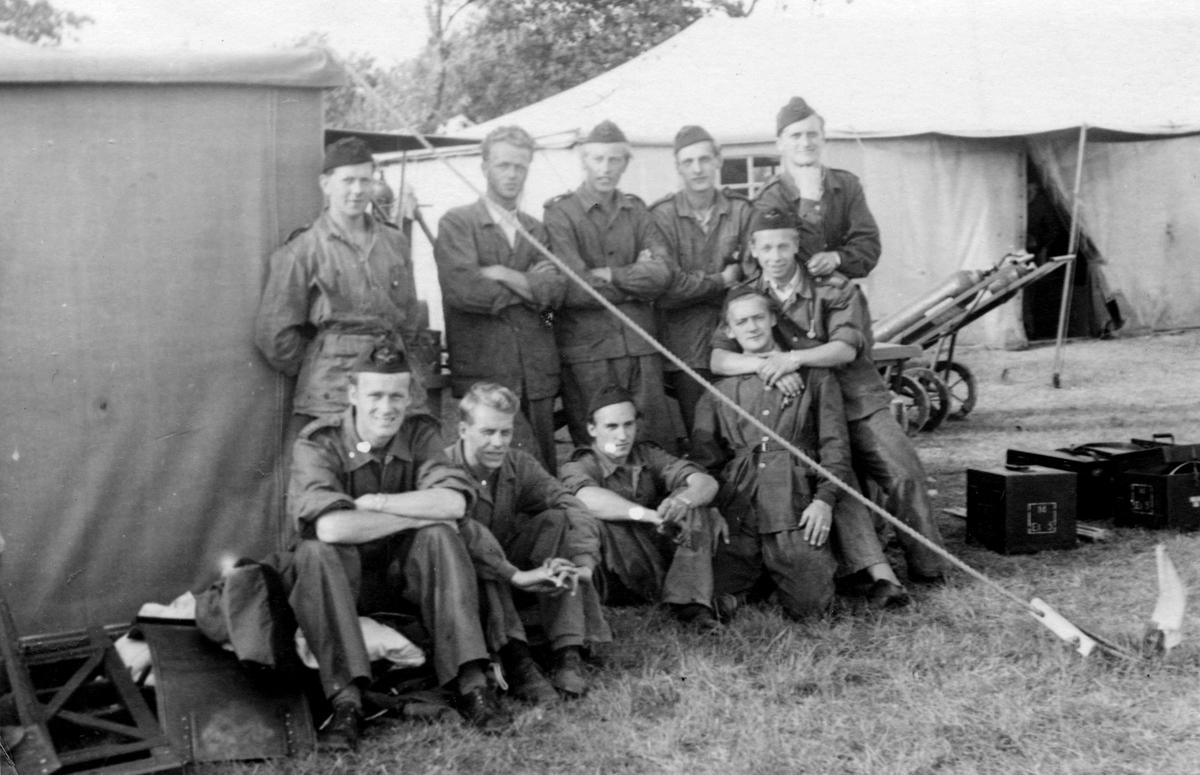 Grupporträtt av militära flygmekaniker, 1940-tal. Tio män vid en tälthangar.