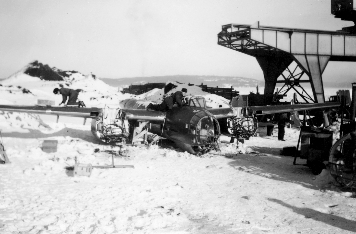 Flygtekniker jobbar med demontering av bärgat flygplan B 18 på kajen i Härnösands hamn efter nödlandning på isen den 10 februari 1946. I bakgrunden syns en lyftkran som användes vid bärgningen.