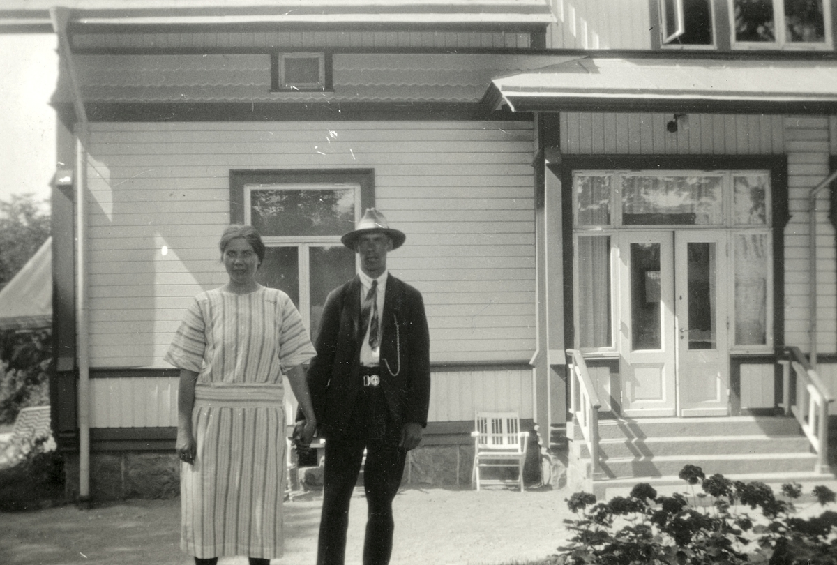 Rut och Fritiof (elev boende på Stretereds skolhem) håller varandra i händerna, ståendes utanför rektorsbostaden i Stretered, 1930-tal.  Relaterat motiv: A2404.