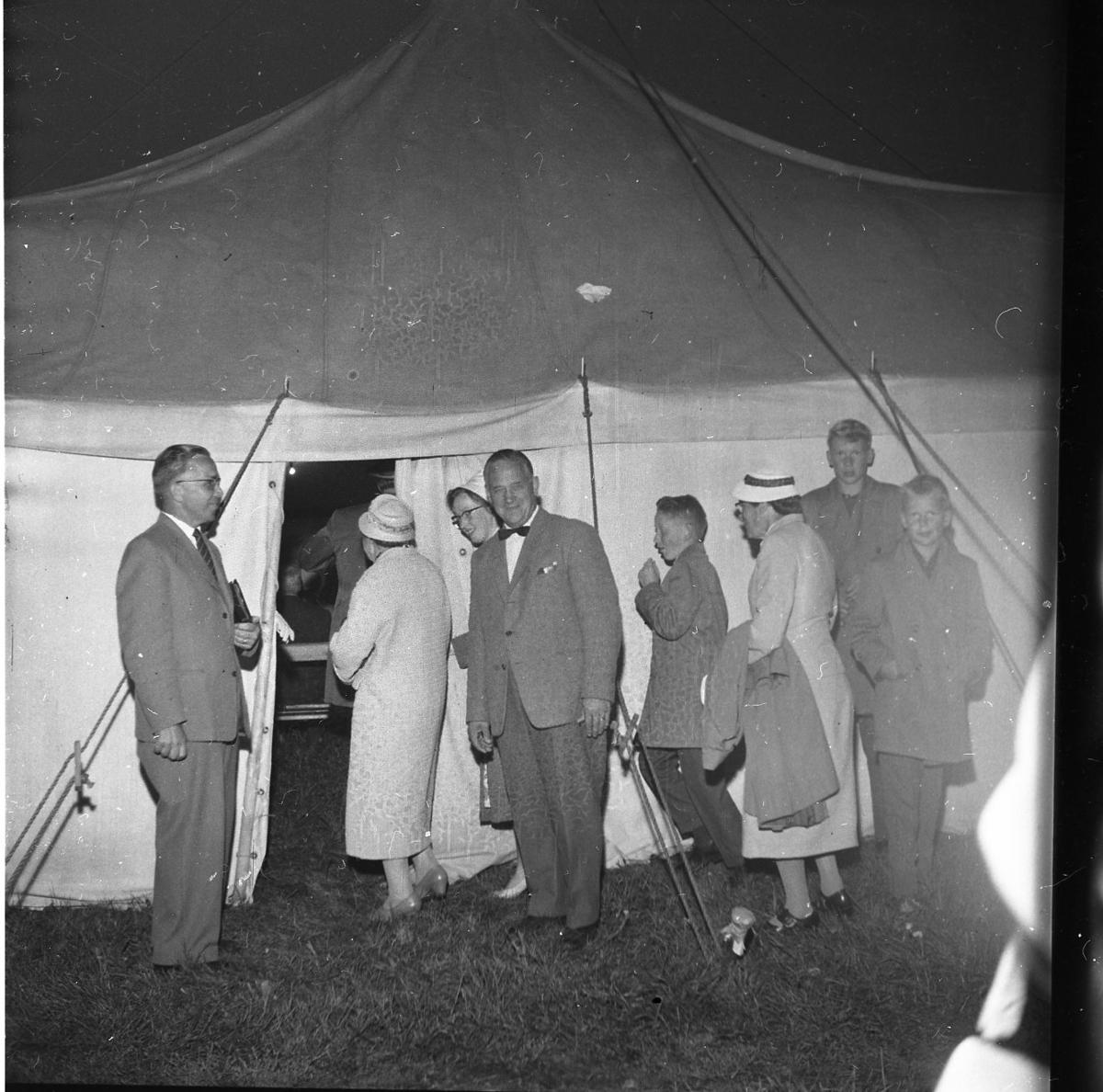 En mindre folksamling på väg in i ett stort tält. Mannen till vänster är pastor Robert Svensson.