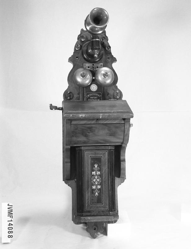 Väggtelefon av plåt och trä. Tallur upptill, själva hörluren saknas. Två ringklockor upptill på framsidan. Nedtill är telefonskåpet dekorerat med ett stiliserat blommönster.