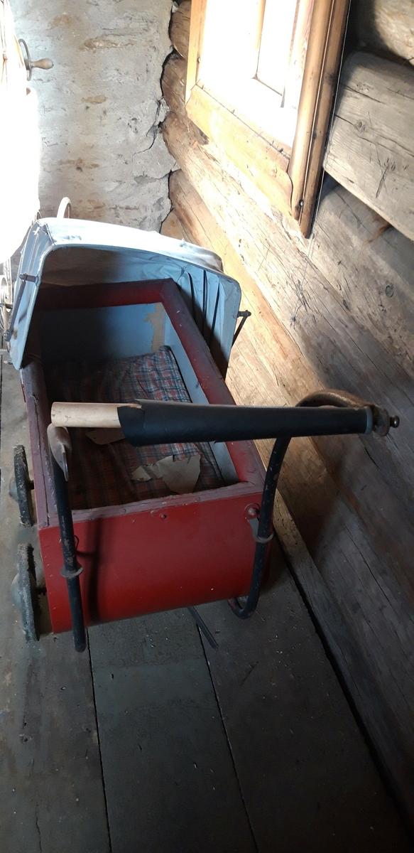 Rødmalt vogn med gråmalt innerside og lys grå kalesje av kunstlær. 4 metallhjul med nedslitt gummidekk. Håndtak av tre med svart plastlignende materiale som er sprøtt. Kalesje med ei flenge. Polstret karm. Mangler skrue i håndtak og kalesje.
