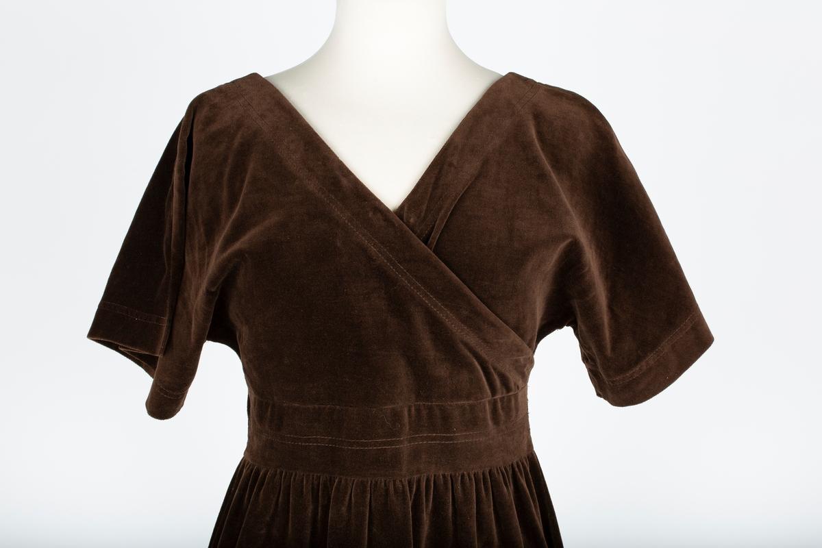 Lang kjole. brun bomullsfløyel. Overdelen har kryssende forstykker, korte kimonoermer, spiss halsringing med pyntestikning forran og bak  Glattllomstykke med pyntestikninger i livet. Skjørt i 3 bredder lett rynket til livets  mellomstykke. Glidelås i ryggen. Splitt i sidene  Kjolen er kjøpt i 1975 hos Elise Brekke, Ski. Forretningen nedlagt mot slutten av 1980-tallet. Kjøpt som penkjole, generell gåbortkjolefordi eier syntes den var lekker.. Bruker og eier Aase Weydahl-Ottesen