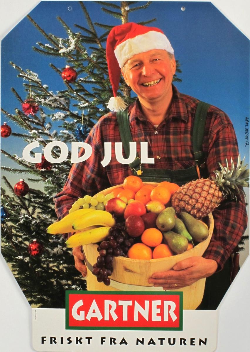 Gartneren med frukt i et trekar, juletre i bakgrunnen.
